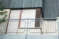 Einfamilienhaus mit durch Hagel beschädigtem Rollladen und Holzfassade